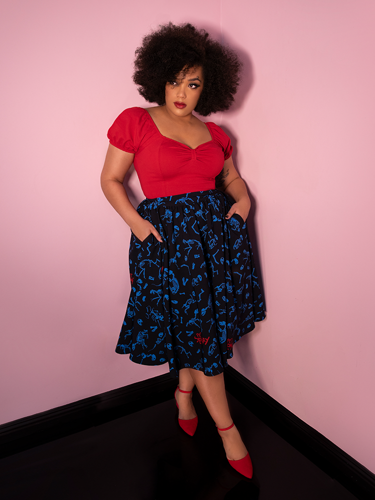 Ashleeta leaning back against a pink wall with her hands in the pockets of her vintage style black skirt while also showing off a peasant top in red.