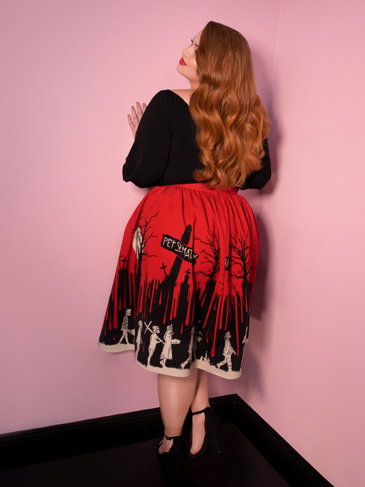 Model Bree stands with her back facing the camera and wearing a spooky retro style outfit with the Pet Sematary Vacation Skirt.