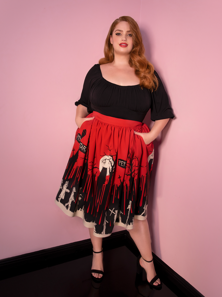 Model Bree glancing directly at the camera with her hands in the pockets of her Pet Sematary red skirt.