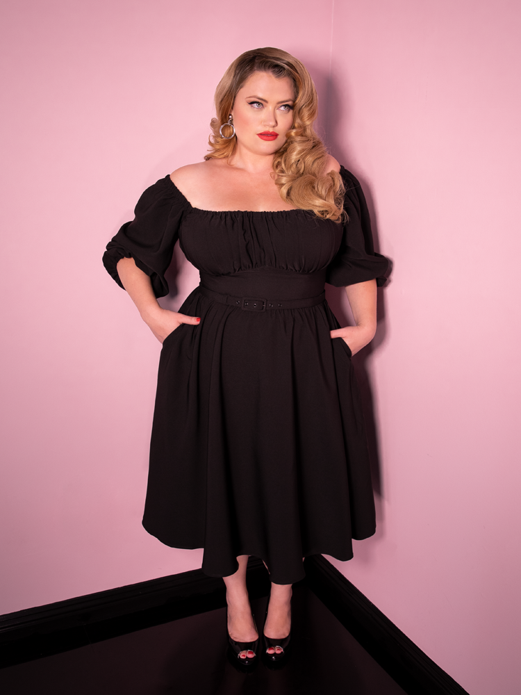Looking away with her hands tucked into her dress, Blondie models the Vacation Dress in Black.