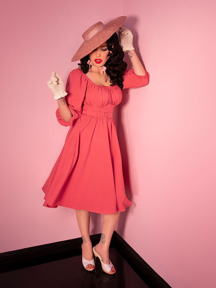 Model in a sun hat wearing a vacation dress in coral pink