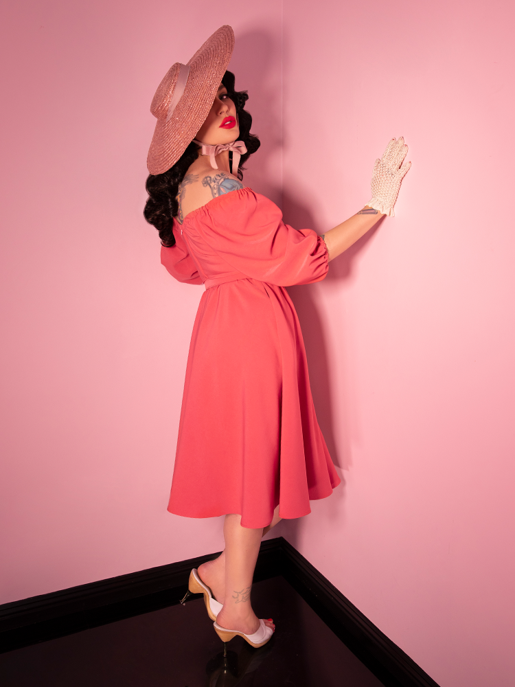 Model in retro dress posing against a pink wall