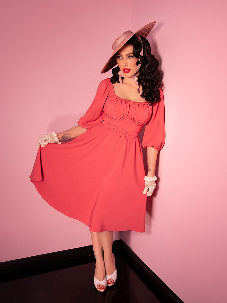 Model posing in a vintage era coral pink dress
