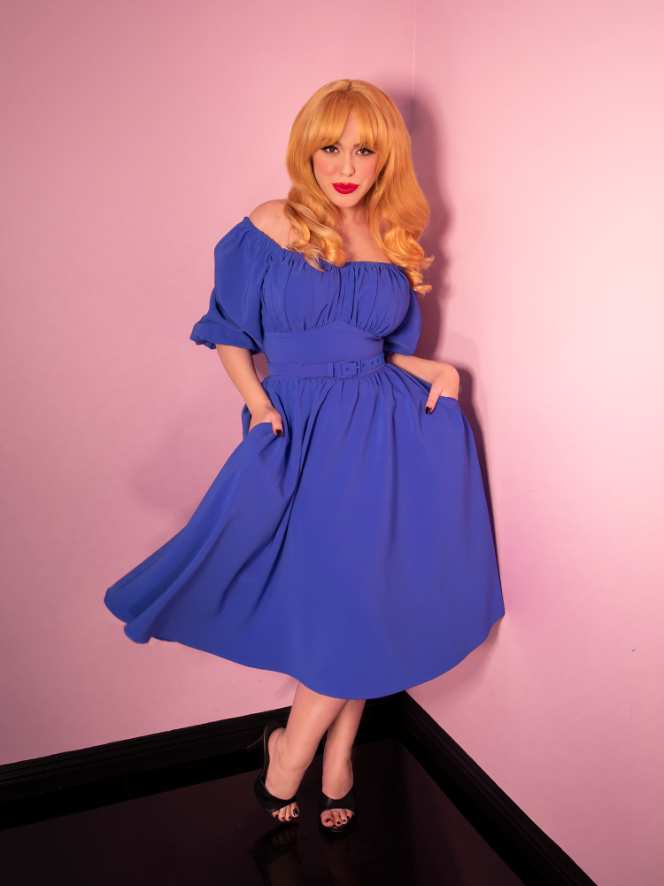 Model posing in a vintage style cornflower blue dress