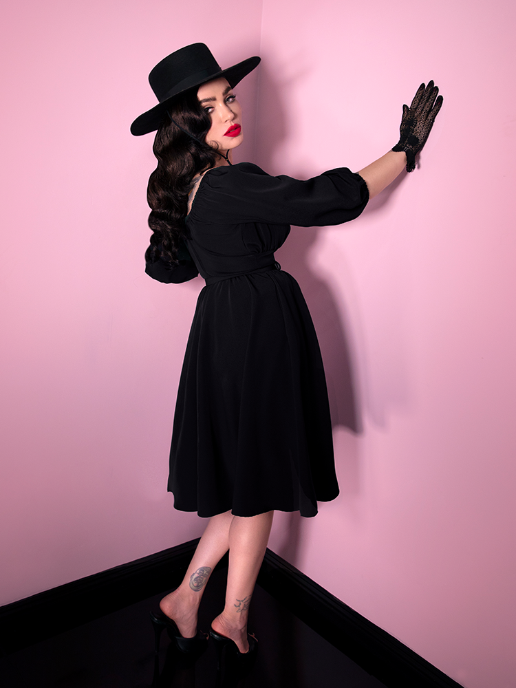Facing a pink wall, Micheline Pitt is turning around to look off camera while wearing a retro style dress in black from Vixen Clothing.