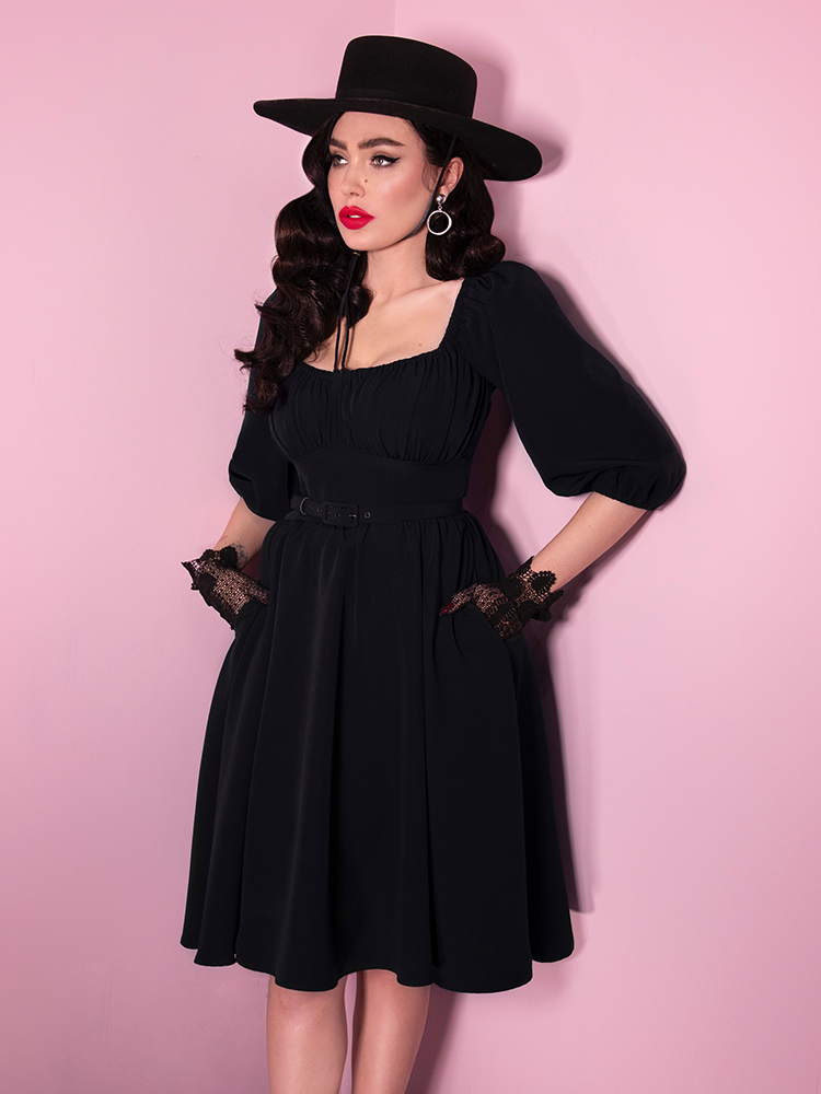 Micheline Pitt wearing a retro era dress in black with matching hat and lace gloves.