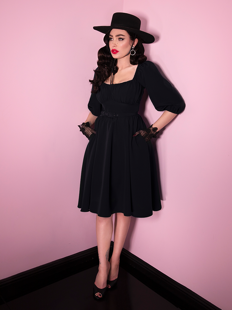 Micheline Pitt sliding her hands into the pockets of her Vacation Dress in Black.