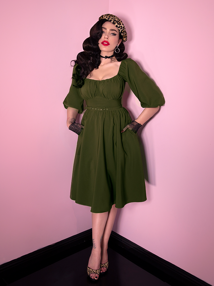 Showing off the pockets, Micheline Pitt looks directly at the camera with her hands tucked into said pockets of the vintage inspired Vacation Dress in Olive Green from Vixen Clothing.