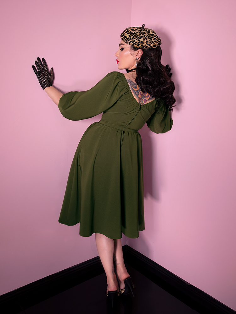 A backshot of Vixen Clothing's latest offering in the Vacation Dress line; this variation comes in an olive green color.