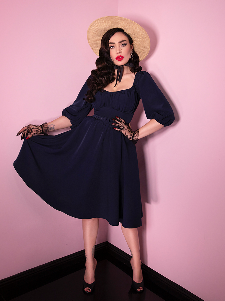A full-body shot of Micheline Pitt wearing the Vacation Dress in Navy Blue.