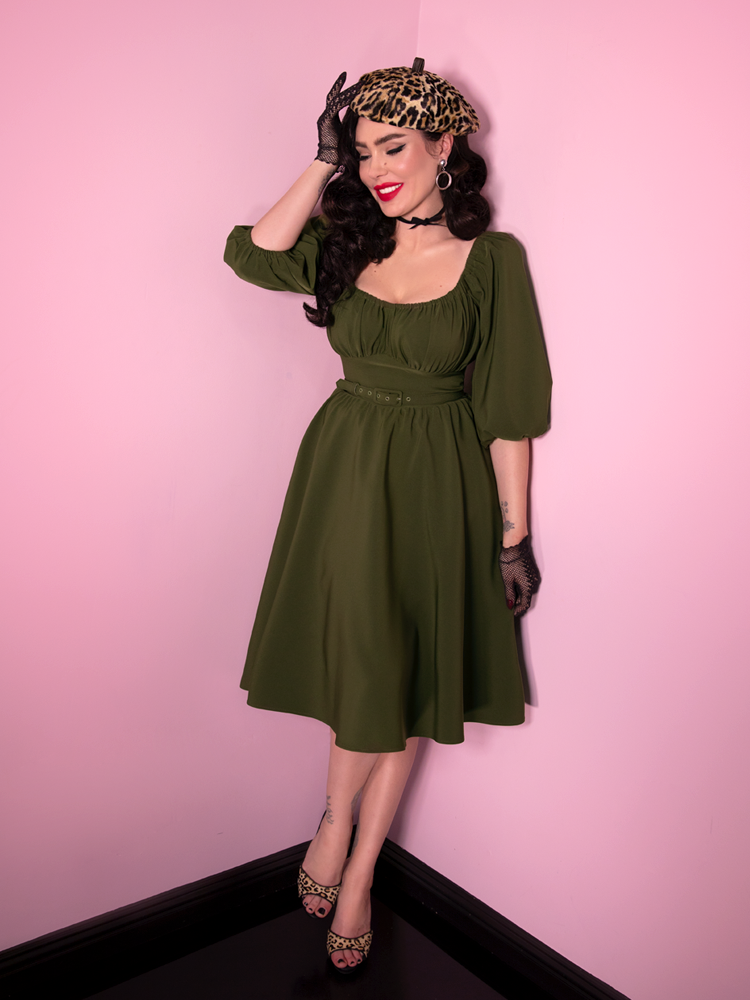 "Full-body shot of Micheline Pitt wearing a retro inspired dress from Vixen Clothing. The dress is called the ""Vacation Dress"" and is shown in an olive green color."