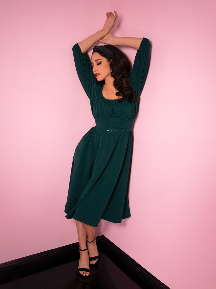 Milynn Moon leaning against pink walls with her arms stretched out over her head wearing the Vacation Dress in Spruce Green from Vixen Clothing.