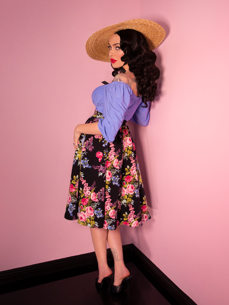 Back shot of Micheline Pitt wearing a vacation swing skirt in a black vintage floral print along with a cornflower blue blouse and natural sunhat.