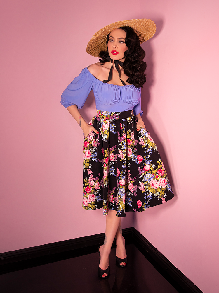 Micheline Pitt wearing a black vintage era flora print skirt with blue top and natural sun hat.