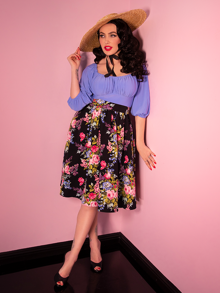 Model Micheline Pitt leaning against a wall wearing a retro style blouse and black vintage floral print vacation swing skirt