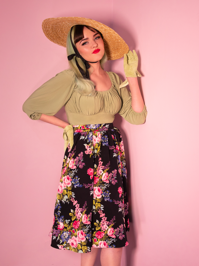 Black floral vintage vacation swing skirt being worn by a model in a sun hat and retro style top