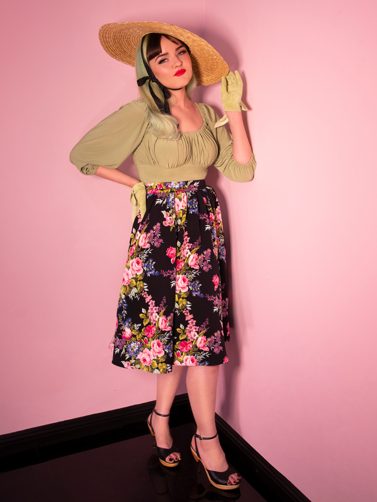 Full body shot of blonde model wearing a floral print skirt while also wearing a vintage looking top in sage green color.