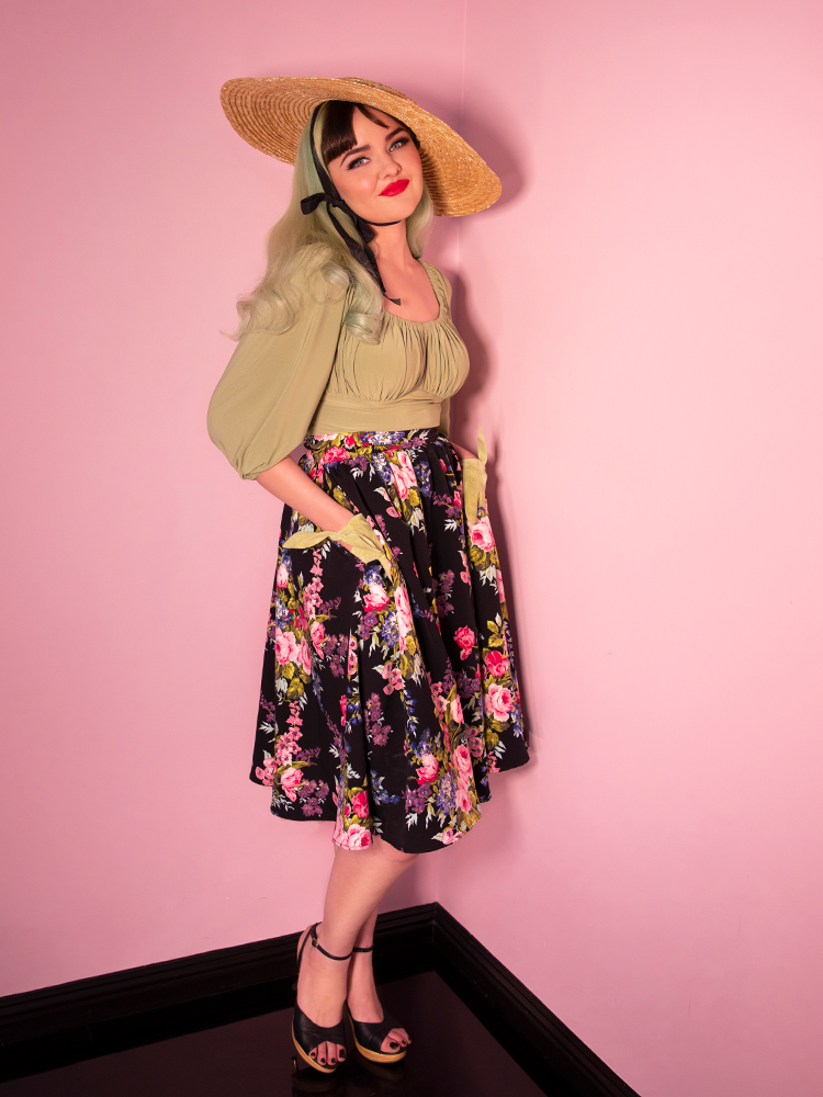 Model standing with her hands in her pockets sporting a naturally colored sunhat, sage green vintage inspired top, a black skirt with brightly colored floral print pattern.