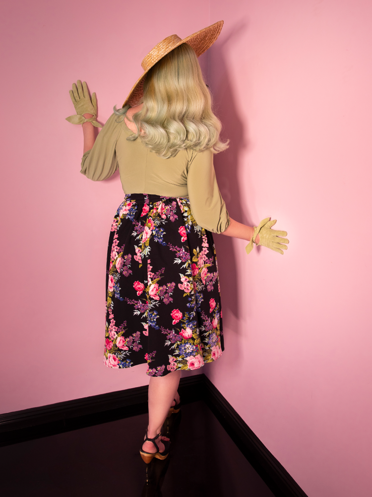 Back shot of blonde model wearing a black vintage floral print skirt and long sleeve olive top.