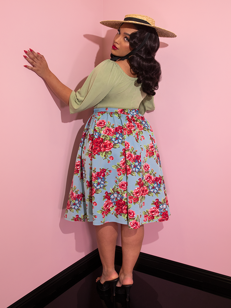Ashleeta wearing a straw hat and green top looking over her shoulder modeling the Vacation skirt in blue and red rose print.