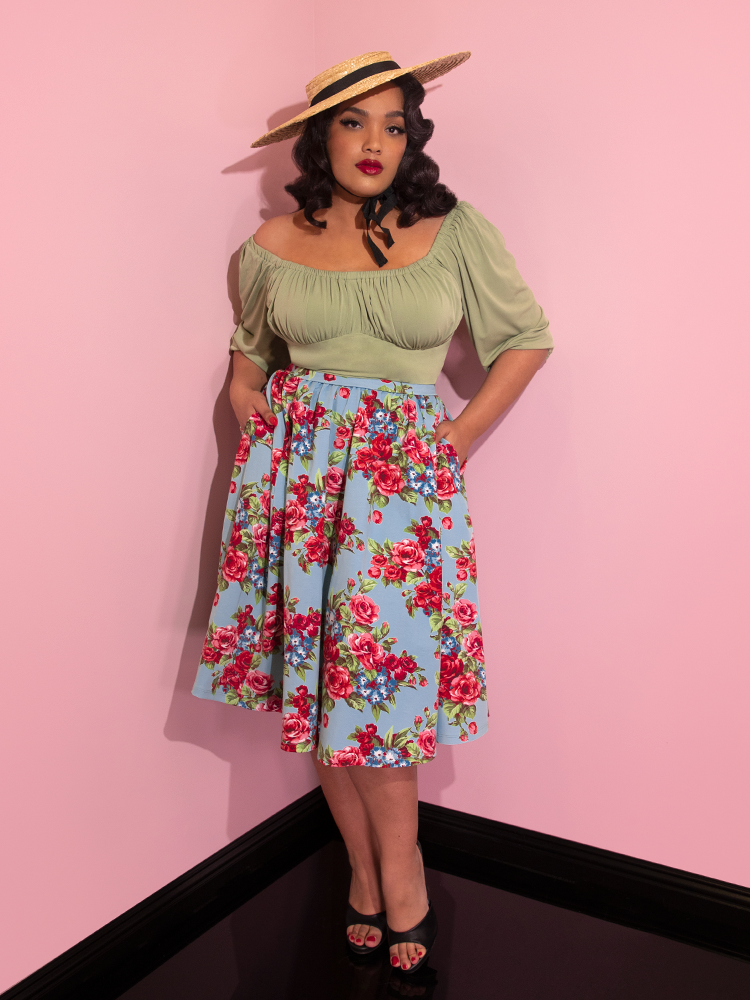 Ashleeta wearing a straw hat and green top modeling the Vacation skirt in blue and red rose print with her hands in her pockets.