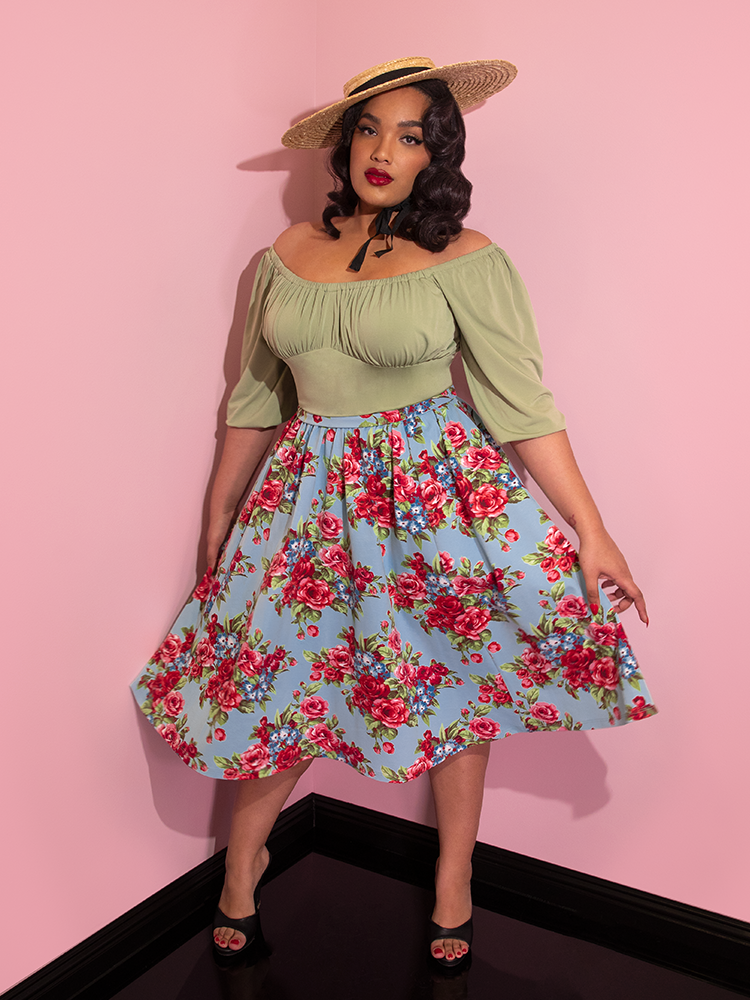 Ashleeta wearing a straw hat and green top modeling the Vacation skirt in blue and red rose print.