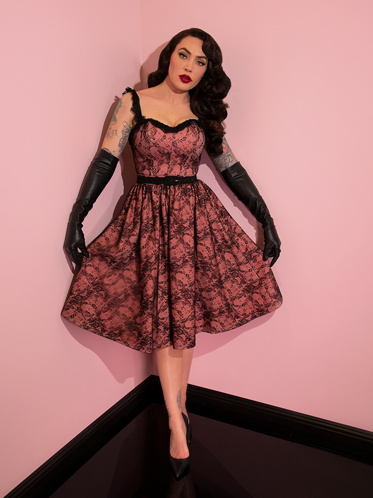 Micheline Pitt shows off the print on her Vacation Swing Skirt in Peach and Black Lace from retro clothing company Vixen Clothing.