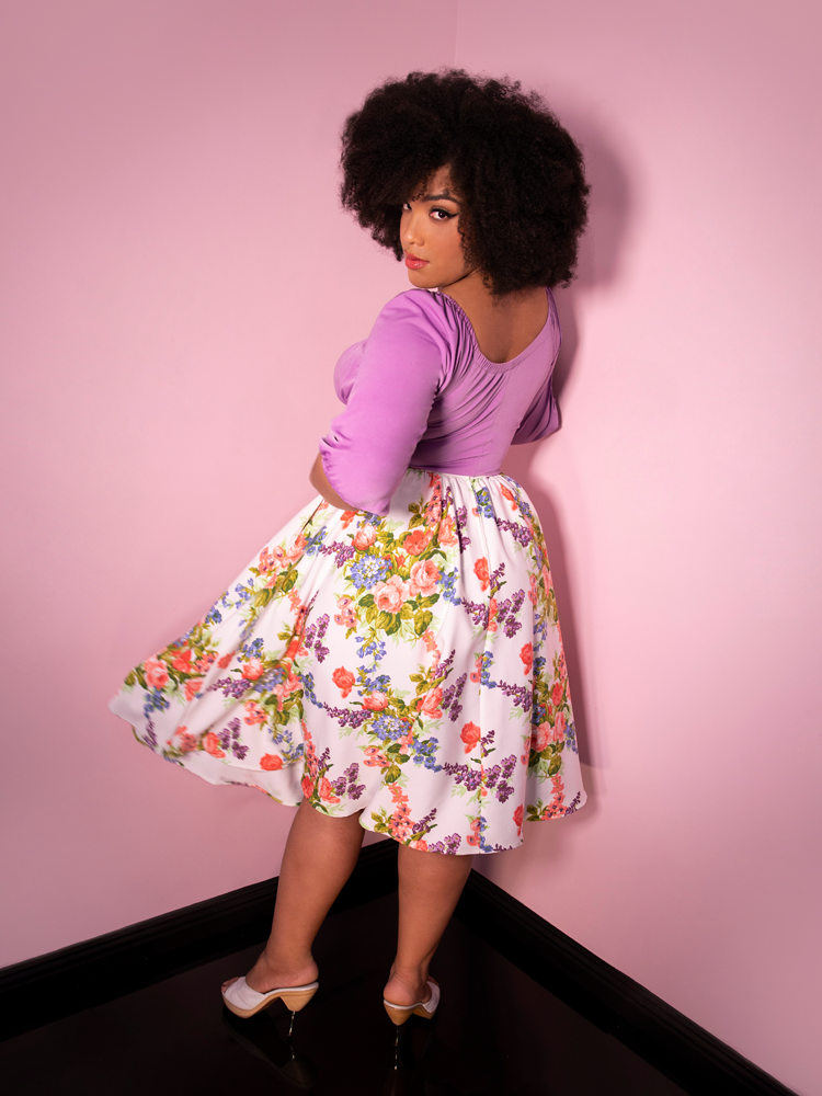 Back shot of model Ashleeta wearing a Vacation Swing Skirt in White Vintage Floral Print from Vixen Clothing along with a low-cut lavender retro top.