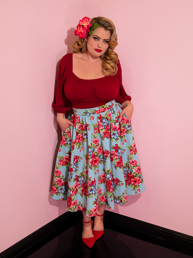 Blondie wearing flowers in her hair and a red top modeling the Vacation skirt in blue and red rose print with her hands in her pockets.