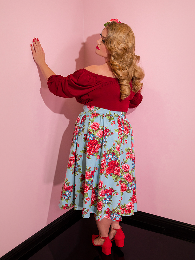 Blondie looking towards the wall wearing a red top modeling the Vacation skirt in blue and red rose print.