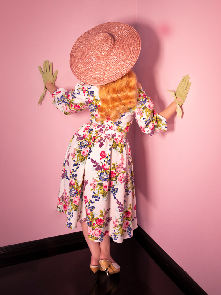 Back shot of model wearing a pink sun hat and a vintage era vacation swing skirt