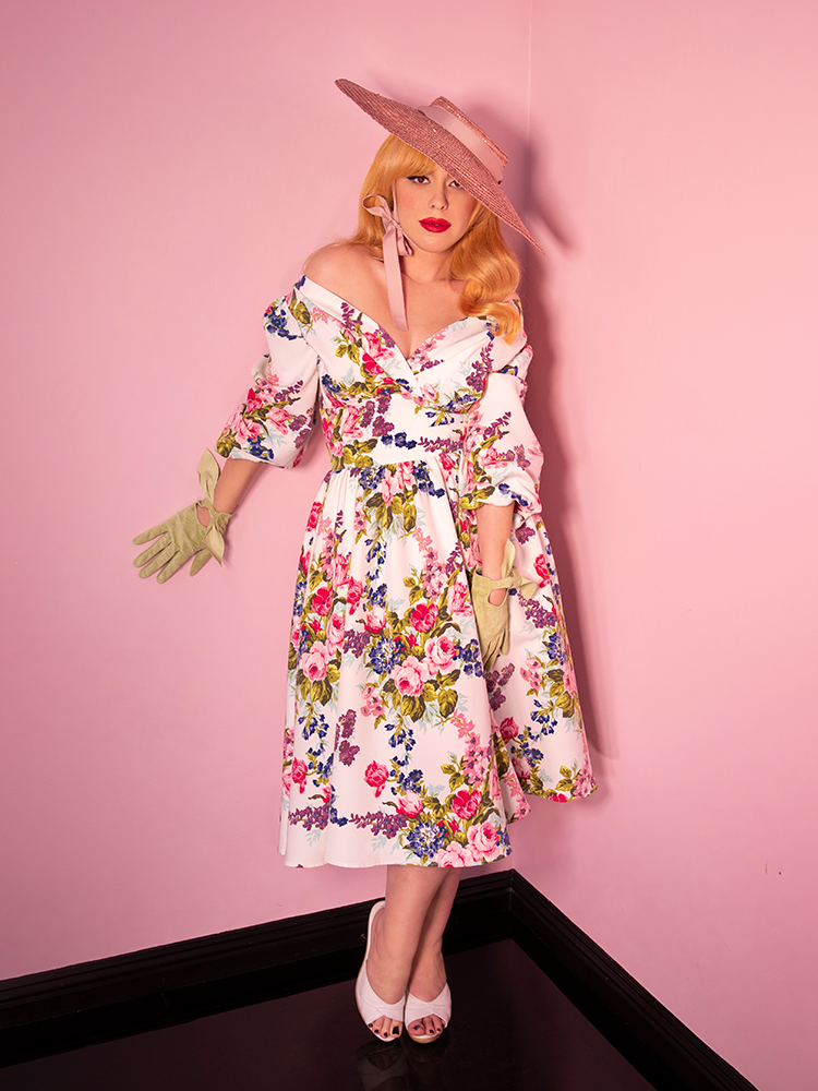Blonde model standing against a pink wall wearing a retro inspired white floral vintage dress