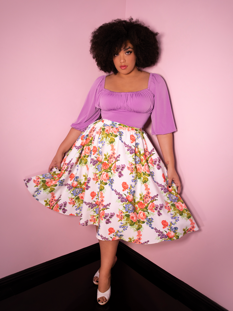 Full body picture of model Ashleeta wearing the Vacation Swing Skirt in White Vintage Floral Print from Vixen Clothing.