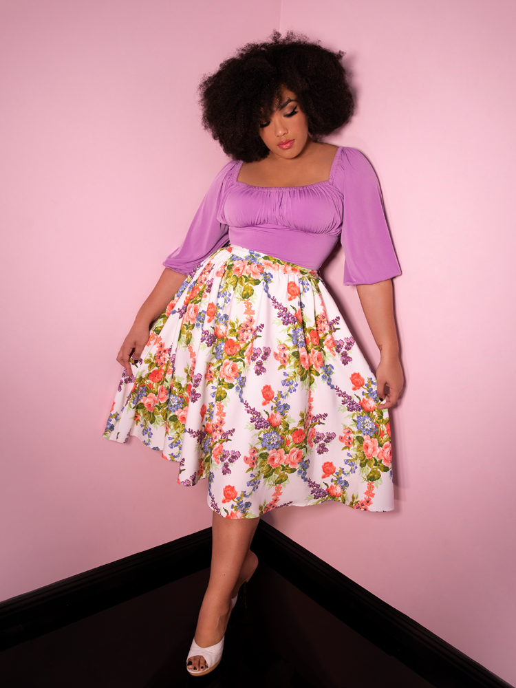 Model Ashleeta wearing a white skirt with floral print and lavender top all from Vixen Clothing.