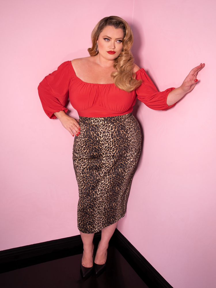Blondie looking off camera modeling the Vacation top in coral red by Vixen Clothing paired with a leopard pencil skirt.