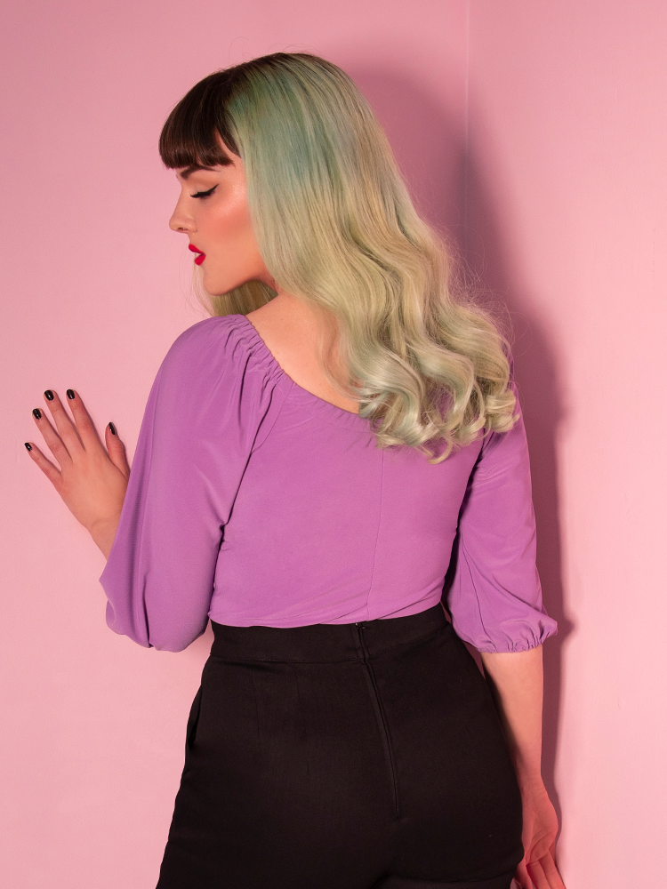 Back shot of model in a lavender vacation blouse and black high waisted pants.