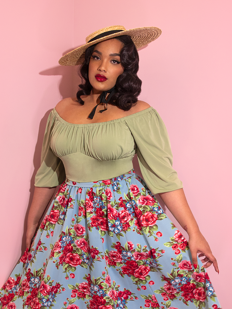 Closeup of Ashleeta modeling the Vacation top in sage green paired with a straw boater hat and blue floral skirt.