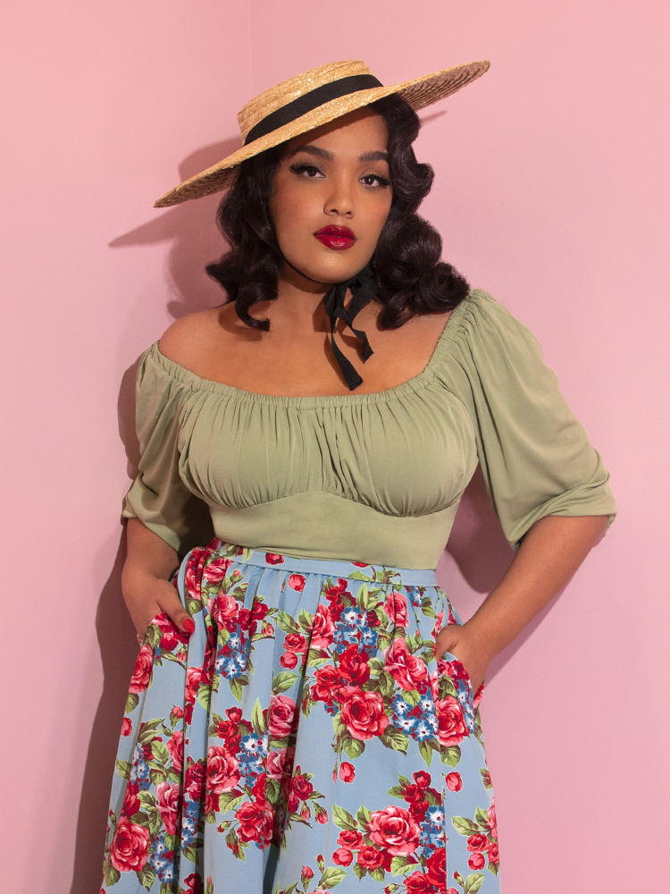 Closeup of Ashleeta looking at the camera with her hands in her pockets modeling the Vacation top in sage green paired with a straw boater hat and blue floral skirt.