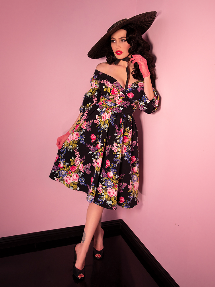 Leaning against a pink wall wearing a vintage style vacation swing skirt in a black floral print, a model looks off camera.