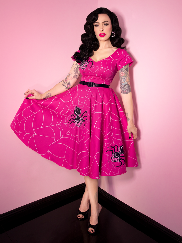 Full image shot of Micheline Pitt wearing a retro spiderweb print dress from Vixen Clothing.