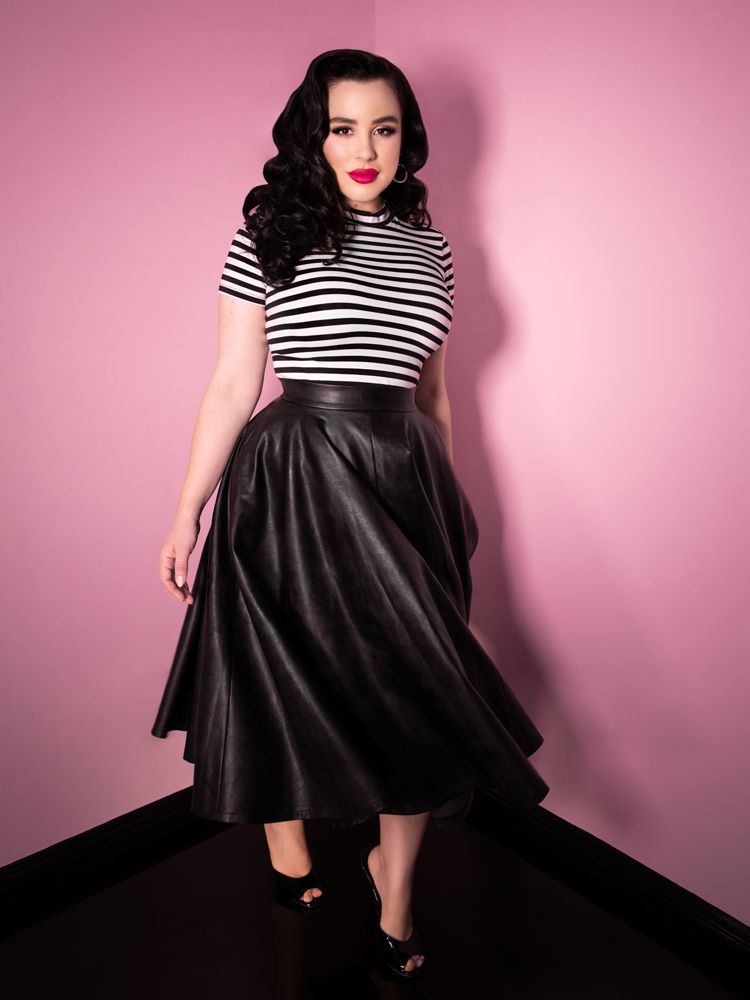 Model Rachel Sedory wearing a black and white striped top and long vegan leather skirt from vintage clothing brand Vixen Clothing.