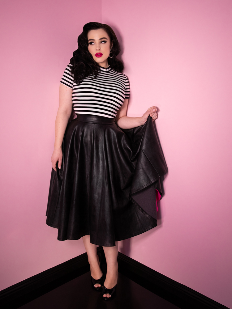 Playfully glancing off to her left, model Rachel Sedory wears the Bad Girl Circle Skirt in Vegan Leather from Vixen Clothing. Also pictured is a black and white striped top.
