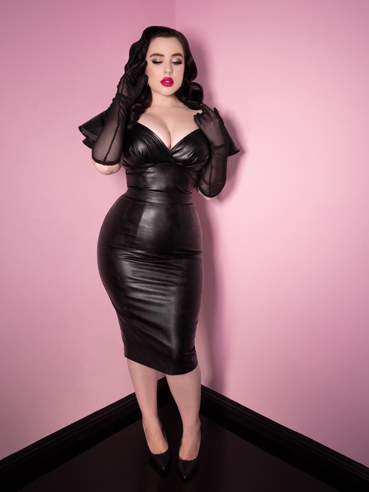 Rachel Sedory looks like she was plucked straight from a 1930s film in her Bad Girl Pencil Skirt in Vegan Leather and matching top along with see through black elbow length gloves from Vixen Clothing.