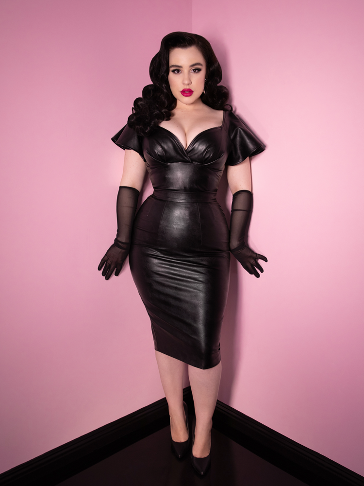 Model Rachel Sedory channels her inner retro dominatrix look with the Bad Girl Babydoll Crop Top in Vegan Leather while also wearing a matching skirt and black lace gloves.
