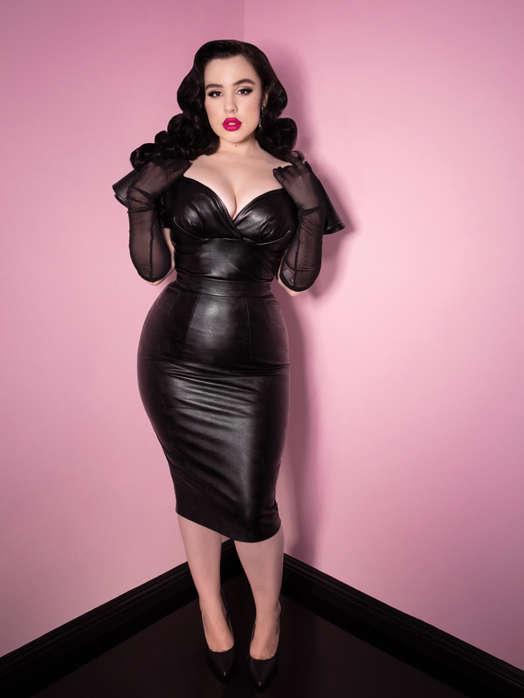 Posing with her hands placed on the front of her shoulders wears the Bad Girl Pencil Skirt in Vegan Leather from Vixen Clothing.