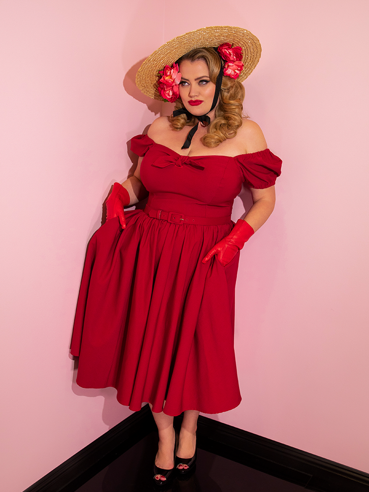 Blondie with her hands in her pockets of the Vixen Swing Dress in Red.