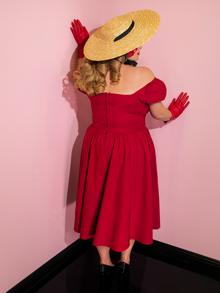 Blondie turned away from the camera to show off the back of her red retro dress.