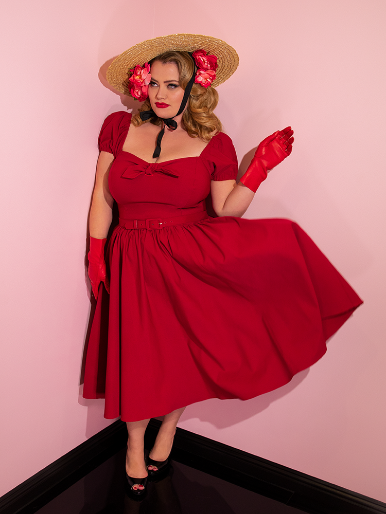 Full length shot of Blondie in a red retro dress paired with a natural colored sunhat.