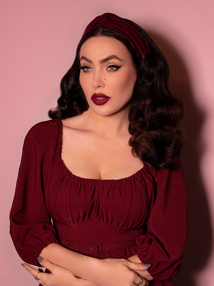 A closeup shot of Micheline Pitt looking past the camera while modeling the knot headband in burgundy paired with a matching dress.