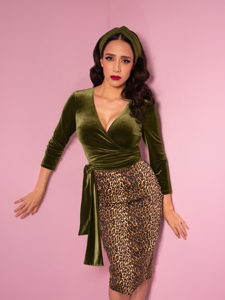 Milynn Moon models a retro style top in olive green along with a vintage inspired leopard print pencil skirt - all items from Vixen Clothing.